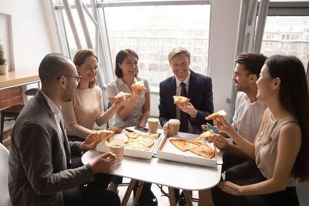 Happy diverse employees having fun, enjoying pizza together, colleagues sharing meal at lunch break, office workers team eating Italian fast food, laughing at funny joke, good relations