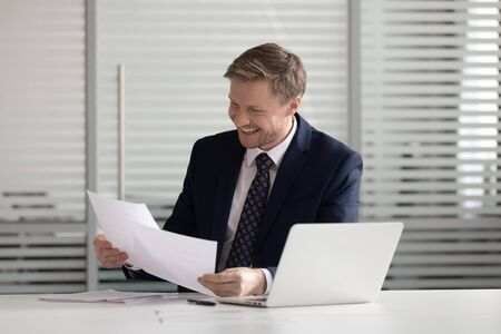 Happy smiling businessman wearing suit holding official documents, paper notification, reading good news in business letter, sitting at office desk with laptop, employee got job or promotion