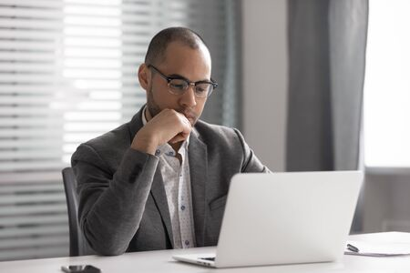 Thoughtful African American businessman wearing glasses using laptop, pondering project, business strategy, puzzled employee executive looking at laptop screen, reading email, making decision Stok Fotoğraf