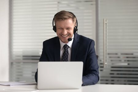 Happy smiling businessman in headset using laptop, working online, confident employee wearing suit consulting client customer or watching webinar, looking at screen, making business video call