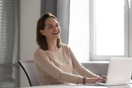 Portrait of happy laughing businesswoman looking at camera, working on laptop in office, female employee having fun at work, feeling positive, sitting at workplace, enjoying funny news Stok Fotoğraf