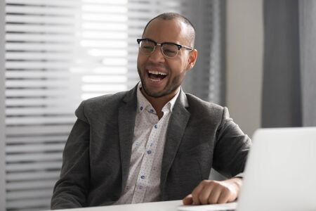 Happy African American businessman wearing glasses laughing at funny joke during break, sitting at desk with laptop, employee intern receive funny news, having fun, feeling joy at office workplace 版權商用圖片 - 131735701