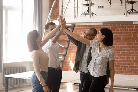 Diverse employees giving high five, celebrating successful deal at meeting in modern office, office workers engaged in team building activity at briefing, motivated for better teamwork result