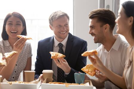 Happy diverse employees colleagues sharing meal at lunch break close up, enjoying pizza, having fun together, office workers team eating Italian fast food, laughing at funny joke, good relations