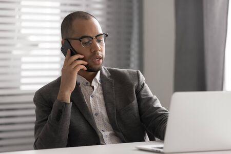 Ernstige Afro-Amerikaanse zakenman met een bril die aan de telefoon praat, laptop gebruikt, een zakelijk gesprek voert, HR-manager die een interview houdt via de mobiele telefoon, een medewerker die klant raadpleegt, een verkoopaanbieding doet Stockfoto