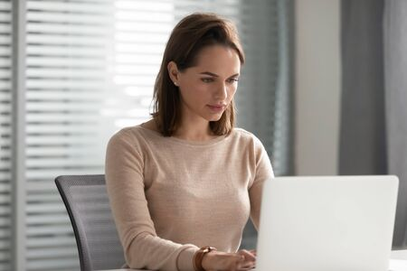 Serious businesswoman using laptop, focused employee or ceo looking at screen, browsing internet, working on online project or writing financial report or business email, sitting at office desk