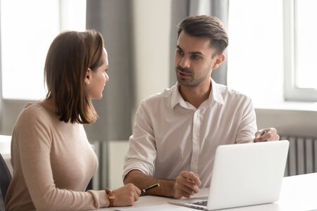 Serious businessman mentor teaching new female employee, helping with corporate software, using laptop, pointing at screen, giving instructions, colleagues working on online project together