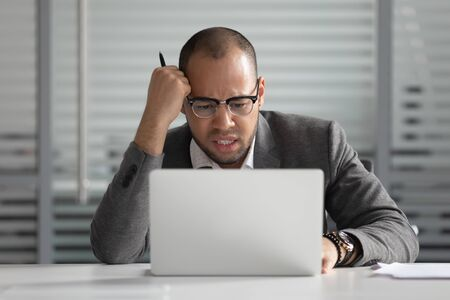 Unhappy African American businessman looking at laptop screen, annoyed employee intern working on difficult online project task, sitting at office desk, receive bad news, notification Stok Fotoğraf