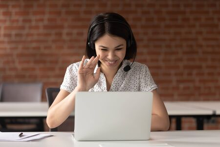 Smiling Asian businesswoman in headset waving hand, using laptop, looking at screen, call center operator consulting client customer, student learning language, mentor teacher training online