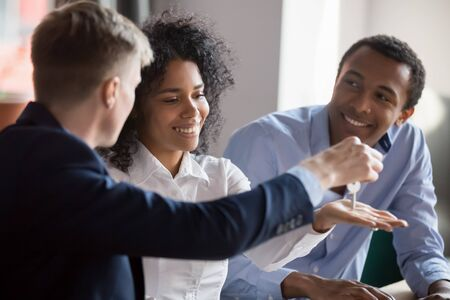Caucasian male realtor or broker give hand keys to excited african american first time buyers couple, happy black husband and wife become owners of shared house, closing deal with real estate agent