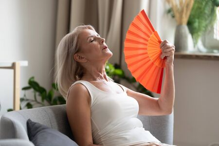 Stressed annoyed old senior woman using waving fan suffer from overheating, summer heat health hormone problem, no air conditioner at home sit on sofa feel exhaustion dehydration heatstroke concept