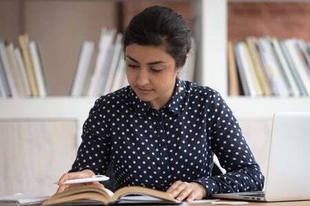 Smart student girl indian ethnicity female sitting at desk turn the pages search or read information, memorizing, prepare for examinations, create essay or practice subject concept of studying process Imagens