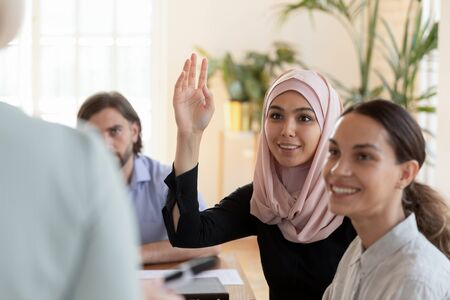 Smiling young asian muslim businesswoman professional training participant leader wear hijab raise hand ask question at diverse corporate group seminar conference meeting, business education concept Stock Photo