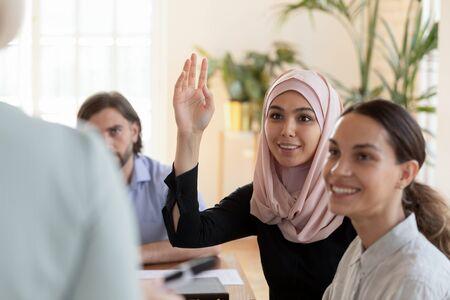 Sonriente joven empresaria musulmana asiática, líder participante de formación profesional, usar hiyab, levantar la mano, hacer preguntas en la reunión de la conferencia del seminario del grupo corporativo diverso, concepto de educación empresarial