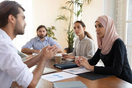 Serious caucasian businessman talking to multicultural business people at meeting table, male manager negotiator mentor teaching diverse team work group consulting clients at conference briefing Stock Photo