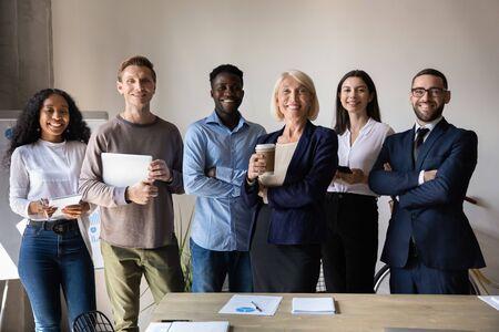 Fröhliche, selbstbewusste, vielfältige alte und junge Geschäftsleute stehen im Büro zusammen, lächelnde multiethnische Berufskollegen, Mitarbeitergruppe Blick auf Kamera, Personalkonzept, Team-Unternehmensporträt