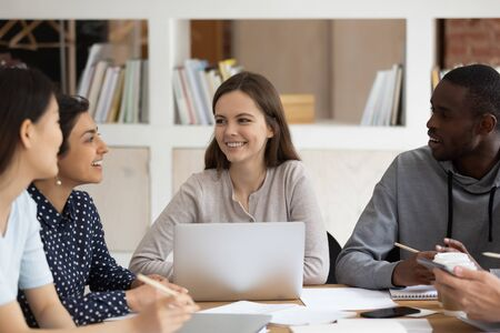 Multi-ethnic students sitting at desk study together, african, indian, asian, european girls and guy preparing for test or exams having friendly warm relationships, learning and racial quality concept Stock fotó