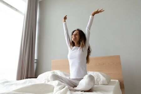 Full length energetic positive young mixed race lady sitting on bed, raising up hands, stretching body after good night rest. Happy biracial woman feeling motivated at weekday start at home.