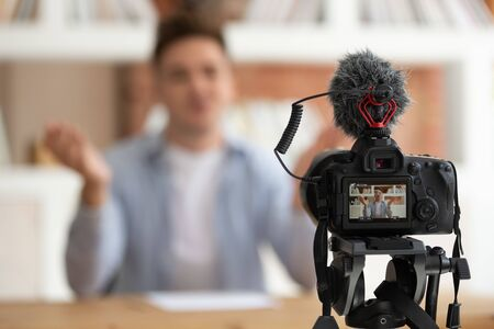 Close up professional digital equipment recording video blog of student shown on screen man sit at desk in front of camera filming online training webinar educational seminar or job interview concept