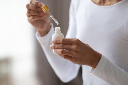 Primo piano giovane donna che tiene la bottiglia con una pipetta, usando olio idratante di cocco o un liquido profumato gradevole. Contenitore di apertura della signora con prodotto cosmetico medico, procedura di bellezza a casa.