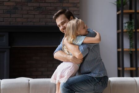 Smiling father hugging cute little daughter wearing princess crown, standing in living room, expressing love and support, young dad and adorable girl cuddling, enjoying tender moment together Imagens
