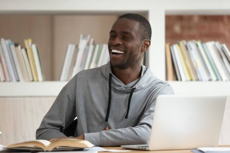 African guy sit at desk in library pc textbook synopsis exercise books on it, student accomplish work look away chatting with friends laughing, university campus studying, friendly environment concept