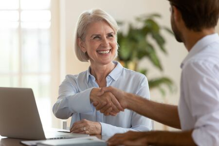 Smiling old mature saleswoman handshake businessman client customer hire job candidate at employment business meeting, happy middle aged bank manager sell loan insurance service shake customer hand