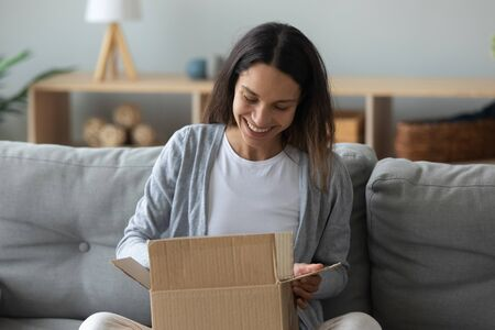 Happy young mixed race woman sitting on couch with cardboard box on knees, unpacking parcel with wished item from popular internet store. Cheerful female client satisfied with fast delivery service.