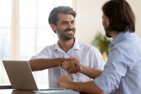 Happy businessman salesman manager handshake satisfied client at business meeting, smiling broker insurer making banking loan insurance investment deal job contract agreement shake customer hand Zdjęcie Seryjne - 132245321