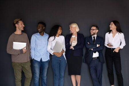 Happy multiracial professional business people laughing together standing in row line near wall, smiling diverse corporate staff young and old employees group having fun, human resource team concept Imagens