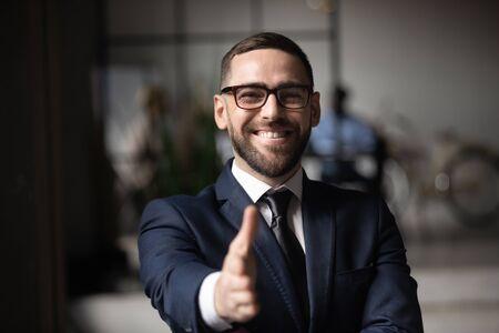 Felice uomo d'affari professionista consulente datore di lavoro venditore indossare tuta estendere la mano alla fotocamera per il concetto di stretta di mano introdurre il saluto offrendo il concetto di collaborazione di collaborazione aziendale, vista ravvicinata