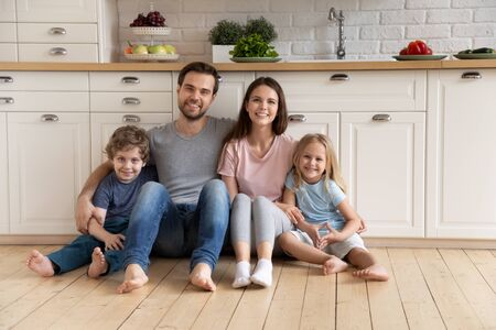 Portrait happy family with children sitting on warm wooden floor in kitchen, smiling father and beautiful mother hugging little cute daughter and son, looking at camera, posing for photo at home