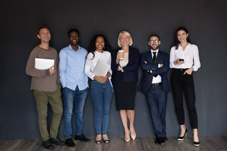 Happy multiethnic professional business people with mature leader stand in row near black wall look at camera, smiling diverse young old human resource corporate staff group, hr team portrait concept Zdjęcie Seryjne - 132245680
