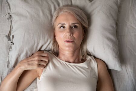 Middle aged mature woman insomniac lying awake in bed looking up trying to sleep, unhappy old senior lady feel disturbed frustrated suffer from insomnia concept uncomfortable bad mattress, top view Imagens