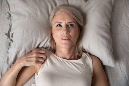 Mujer madura de mediana edad insomne acostada despierta en la cama mirando hacia arriba tratando de dormir, anciana mayor infeliz se siente perturbada frustrada sufre de insomnio concepto incómodo mal colchón, vista superior
