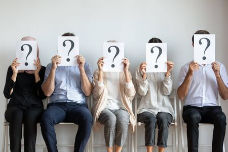 Unemployed professional business people candidates group sit on chairs in row line queue holding sheets with question mark hiding face waiting for job interview, human resources and recruit concept