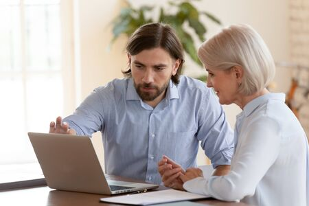 Professional male mentor instructor teaching mature employee help older middle aged worker intern explaining computer software, manager consulting client looking at laptop screen sit at office desk Zdjęcie Seryjne - 132245886