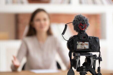 Konzentrieren Sie sich auf den Vordergrundkamerabildschirm, zeigen Sie Live-Aufnahme-Videoblog, selbstbewusste tausendjährige Frau, die vor der Kamera sitzt und Lehrvideos für den Online-Universitätskurs dreht, professionelles Wissen teilen