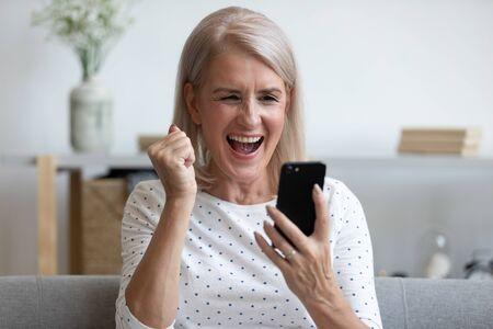 Überglückliche reife alte Frau hält das Telefon mit Blick auf den Bildschirm und freut sich über den Gebotsgewinn für die mobile Online-App, die glückliche Gewinnerin mittleren Alters feiert den Siegerfolg und liest die Nachricht gute Nachrichten in der Zelle zu Hause
