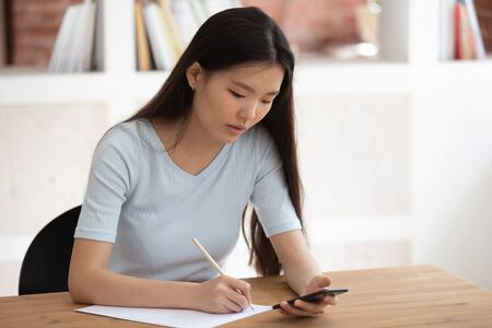 Vietnamese student using app downloaded on phone studying seated at desk, focused girl prepare for university exams writing notes on paper thoughts and helpful info, educational websites usage concept Banco de Imagens - 132121101