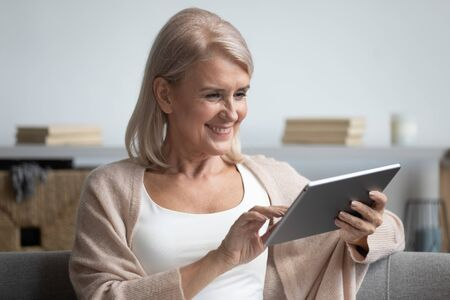 Happy relaxed mature middle aged old adult woman holding device using computer app looking at digital tablet sit on couch reading e book doing internet shopping make online order for delivery at home Zdjęcie Seryjne