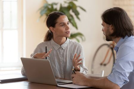 Confident female insurance broker talking to male customer, businesswoman employee consulting businessman colleague with laptop sit at desk, mentor teach intern new worker convince client at meeting Stok Fotoğraf