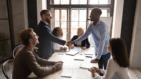 Satisfied diverse male professionals interracial partners investor and client handshake at multiracial team meeting make financial business deal express respect for good teamwork at group negotiation Stock fotó