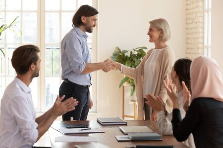 Happy old middle aged female employee get promotion and team appreciation handshake male boss, mature businesswoman worker rewarded for good results in office, respect and recognition at work concept Zdjęcie Seryjne - 132247423