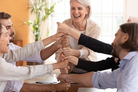 Happy older leader mentor coach unite excited multiethnic employees stack fists together, overjoyed diverse company staff join hands at group meeting building reliable office business team concept