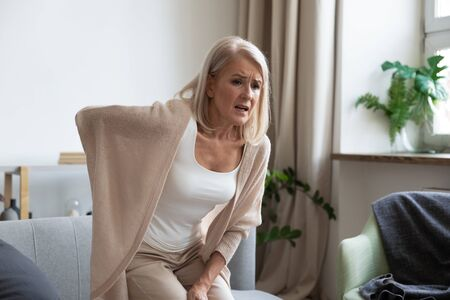 Worried upset middle aged mature woman feel hurt sudden back ache touch sore spine at home alone, tired mature senior grandmother having lower lumbago backache injury spinal pain, backpain concept Standard-Bild