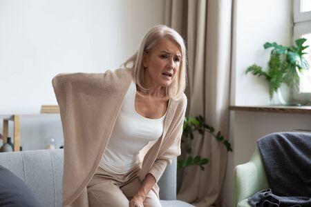 Zmartwiona zdenerwowana dojrzała kobieta w średnim wieku czuje się zraniona nagły ból pleców, dotknięty ból kręgosłupa w samotności w domu, zmęczona dojrzała starsza babcia mająca niższy ból pleców lumbago ból kręgosłupa, koncepcja bólu pleców