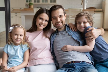Portrait happy family, parents with little kids, children hugging, sitting on couch, smiling beautiful mother and father with cute daughter and son looking at camera, posing for photo at home