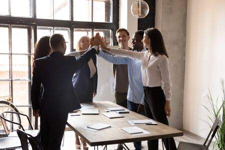 Happy motivated multiracial office people group giving high five in company meeting room engaged in celebrating good cooperation result, corporate success, help power in building dream team concept