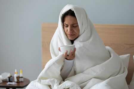 Sad unhealthy young biracial woman suffering from freezing, covering in blanket with head, holding cup of hot tea or cold medicine. Millennial lady caught cold, treating herself alone at home. Stock Photo